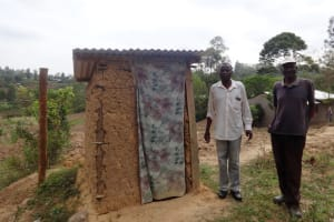 The Water Project: Shitungu Community B, Charles Amala Spring -  Charles And Andrew Amala Stand By Their Household Latrine