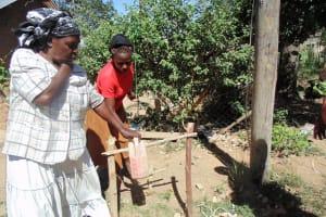 The Water Project: Shiamboko Community, Oluchinji Spring -  Mrs Oluchinji And Her Daughter With An Improvised Handwashing Container