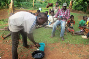 The Water Project: Eluhobe Community, Amadi Spring -  Silas Mutie Demonstrates How To Wash Hands With Water And Ash