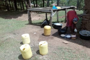 The Water Project: Muhudu Primary School -  Cook Washing Utensils