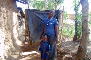 The Water Project: Shiamboko Community, Oluchinji Spring -  Claire Poses With Her Son Next To Her Bathroom