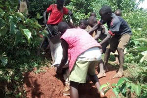 The Water Project: Eluhobe Community, Amadi Spring -  Children Passionately Helping To Ferry Cement Along A Rugged Terrain To The Spring Construction Site