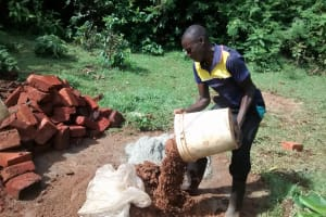 The Water Project: Eluhobe Community, Amadi Spring -  Community Member Helps With Cement Work