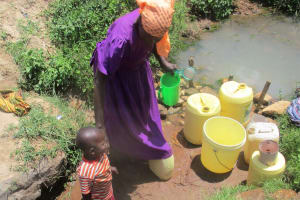 The Water Project: Mulundu Community, Fanice Mwango Spring -  Women Bring Their Children With Them To Fetch Water