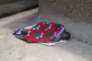 The Water Project: Mulundu Community, Fanice Mwango Spring -  A Kid Ailing From Malaria Sleeping Outside Her House With No Medical Attention