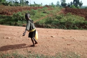 The Water Project: Shikhuyu Community -  Small Child Carrying Water