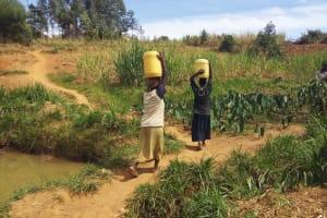 The Water Project: Futsi Fuvili Community, Futsi Fuvili Spring -  Women Carrying Water