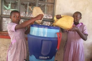 The Water Project: Lwangele Primary School -  Girls Fill The Broken Filter With Stream Water