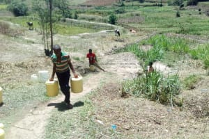 The Water Project: Handidi Community, Malezi Spring -  Alex Carrying Water