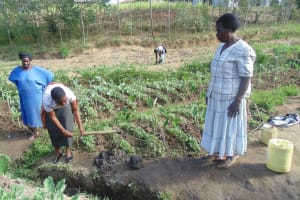 The Water Project: Shiamboko Community, Oluchinji Spring -  Rose A Wewasafo Staff Helps Community Clear Its Drainage Trench