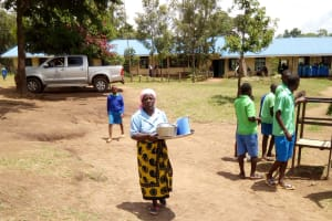 The Water Project: Musunji Primary School -  Cook Taking Tea To Staff