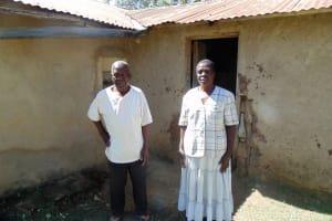 The Water Project: Shiamboko Community, Oluchinji Spring -  Mr And Mrs Oluchinji Outside Their Home