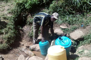 The Water Project: Handidi Community, Matunda Spring -  Zablon Fetching Water At Matunda Spring