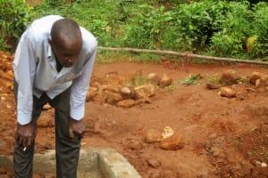 The Water Project: Mutambi Community, Kivumbi Spring -  Community Member Watches Pipe Installation