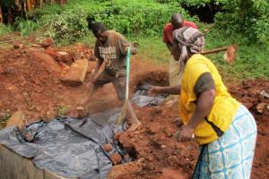 The Water Project: Mutambi Community, Kivumbi Spring -  Community Members Help Backfill