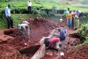 The Water Project: Mutambi Community, Kivumbi Spring -  Community Members Watch Final Stages
