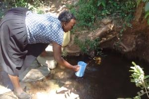 The Water Project: Irenji Community, Shianda Spring -  Mrs Lukanda Fetching Water