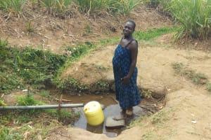 The Water Project: Futsi Fuvili Community, Shikanga Spring -  Mrs Alice Aliyo Fetching Water
