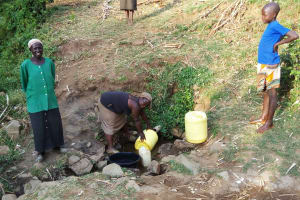 The Water Project: Mumuli Community, Shalolwa Spring -  Fetching Water