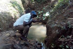 The Water Project: Elunyu Community, Saina Spring -  Mr Erastus Chimwadi Drinking Water From The Spring