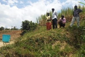 The Water Project: Mukhuyu Community, Shikhanga Spring -  Villagers Watch As We Inspect Their Spring