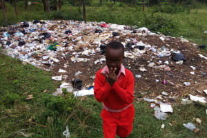 The Water Project: Mumias Central Primary School -  Student Posing In Front Of Trash