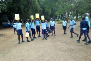 The Water Project: Mumias Central Primary School -  Students Returning With Fetched Water