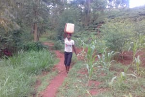 The Water Project: Visiru Community, Kitinga Spring -  Alice Balances A Jerrycan Full Of Water From The Newly Constructed Kitinga Spring