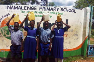The Water Project: Namalenge Primary School -  Students Posing With Water Containers At School Entrance