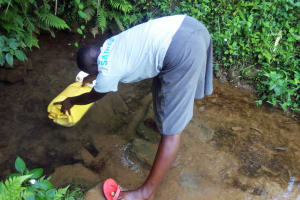 The Water Project: Hondolo Community, Musila Spring -  Lady Fetching Water At Musila Spring
