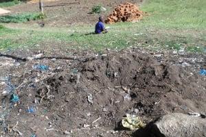 The Water Project: Shiyunzu Primary School -  Boy Seen Reading Next To School Dump