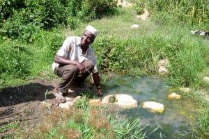 The Water Project: Chegulo Community, Shakava Spring -  Mr Shakava Removing Contaminants