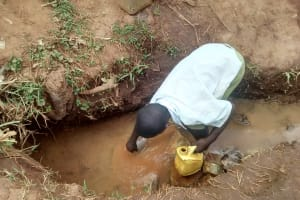 The Water Project: Lugango Community, Lugango Spring -  Andrew Fetching Water