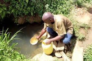 The Water Project: Kakubudu Community, Fred Lagueni Spring -  Village Elder Fetching Water