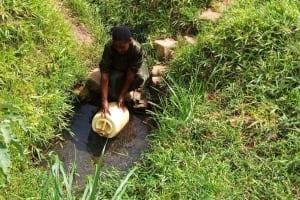 The Water Project: Bushevo Community, David Enani Spring -  Mrs Enani Fetching Water Cropped