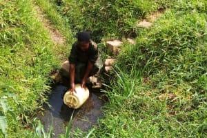 The Water Project: Bushevo Community, David Enani Spring -  Mrs Enani Fetching Water