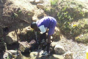 The Water Project: Ematiha Community, Ayubu Spring -  Student Drinking Spring Water