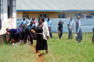 The Water Project: Ebubayi Secondary School -  Principal Leading Her Students To Pick Up Litter