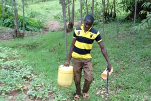 The Water Project: Irungu Community, Irungu Spring -  Mr Ainea Kavoje Carries Water From The Spring
