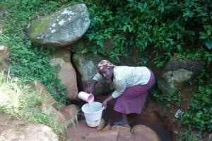 The Water Project: Gidagadi Community, Anusu Spring -  Mrs Sayo Scooping Water At The Spring