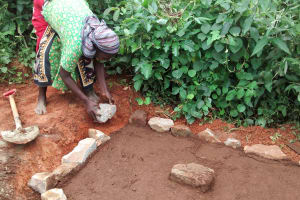 The Water Project: Wamuhila Community, Isabwa Spring -  Alice Imali Helping The Artisan To Set The Place For Casting Her Latrine Slab