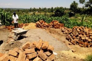 The Water Project: Kalenda Primary School -  Artisans Working On Latrine Foundation