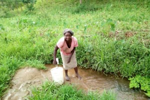 The Water Project: Shitungu Community, Mmbone Spring -  Fetching Water