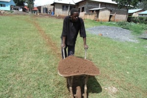 The Water Project: Ebukanga Secondary School -  A Community Member Brings Materials To Construction Site