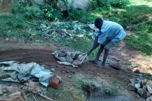 The Water Project: Lugango Community, Lugango Spring -  Man Delivering Stones To The Spring
