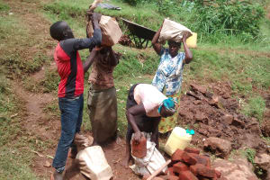 The Water Project: Lugango Community, Lugango Spring -  Women Carrying Construction Materials