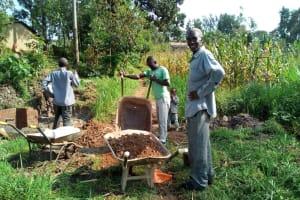The Water Project: Handidi Community, Kadasia Spring -  Community Members Transporting Materials