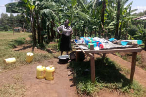 The Water Project: Gidagadi Secondary School -  Cook Stands Proudly By Dish Rack