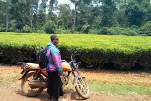 The Water Project:  Field Officer Joan Were Poses Next To A Tea Plantation Opposite The School