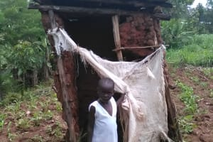 The Water Project: Mwichina Community, Mwichina Spring -  A Girl Stands By Her Latrine